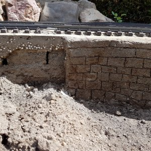 Bricks and rubble underground covered with concrete - styro balls mix. Stone wall